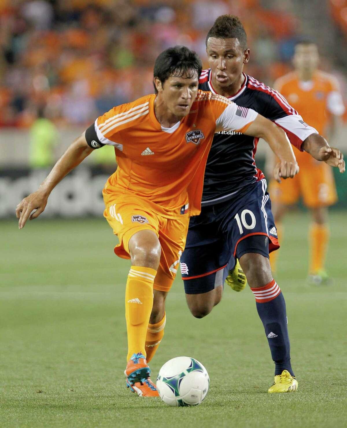 5/18/13: Houston Dynamo forward Brian Ching (25) dribbles against New England Revolution Juan Agudelo (10) in the second half at BBVA Compass Stadium in Houston, Texas. New England Revolution won 2 to 0.