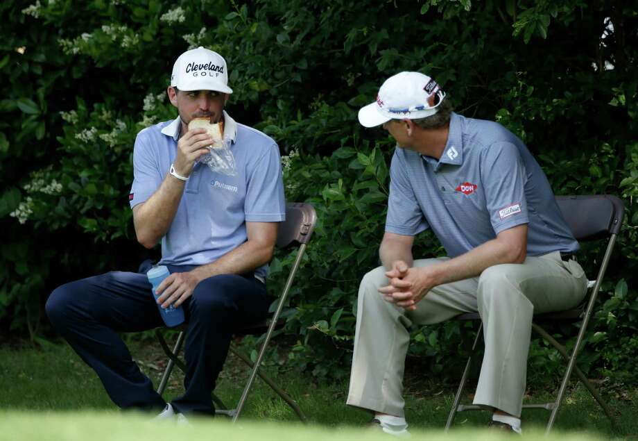 Byron Nelson leader Keegan Bradley grabs a bite to eat as he waits to tee off on No. 15 in the third round. Photo: Tony Gutierrez, STF / AP