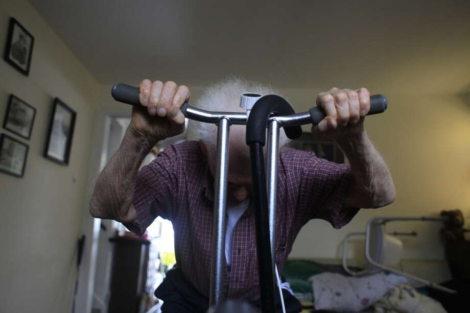 "Determined to get back to the golf course some day, former owner of Red's Java House Tom ""Red"" McGarvey, 85, does excises in his basement after his afternoon walk."