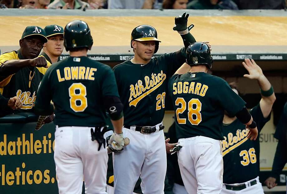 Josh Donaldson (20) and teammates congratulate Jed Lowrie and Eric Sogard, who scored on Lowrie's sacrifice fly. Photo: Ezra Shaw, Getty Images