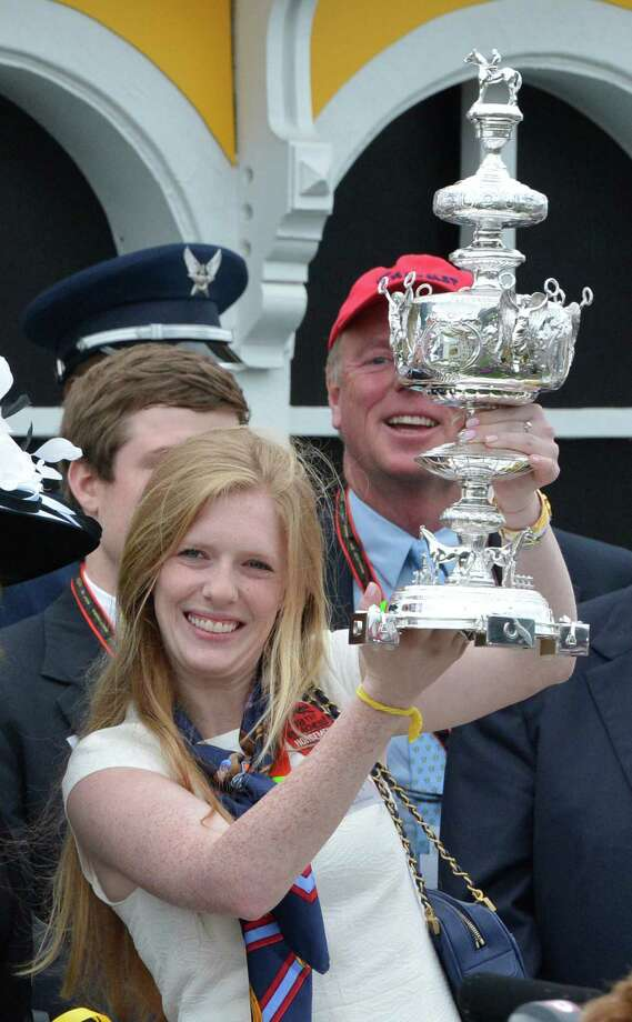 Erin Kelly raises the winner's trophy aloft in the winner's circle after her father's horse Oxbow won the 138th running of the Preakness Stakes May 18, 2013 at historic Pimlico Race Course in Baltimore, Maryland.  This was the second jewel of the thoroughbred racing's triple crown.  Kentucky Derby winner Orb finished fourth.   (Skip Dickstein/Times Union) Photo: SKIP DICKSTEIN