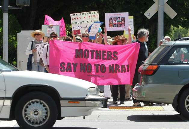 Members of CODEPINK and other women's group pause at stoplight as they march down Capitol Mall to the offices of the National Rifle Association in Sacramento, Calif., Friday, May 10, 2013. The pre-Mothers Day demonstration was held to protest the NRA's opposition to gun control measures.(AP Photo/Rich Pedroncelli) Photo: Rich Pedroncelli, STF / AP