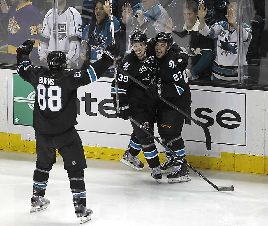 Logan Couture (39) celebrates with Scott Gomez and Brent Burns after his game-winning goal lifted the Sharks in overtime. Photo: Tony Avelar, Associated Press