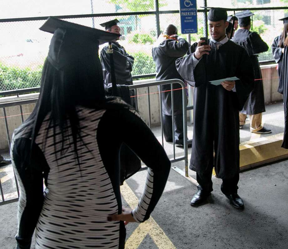 Mike Ross Connecticut Post freelance - Southern Connecticut State University student Christopher Harris snaps a photo of friend Tyniqua Carey at stagging area for Friday morning commencement excerises at Webster Bank Arena. Photo: Mike Ross / Connecticut Post contributed