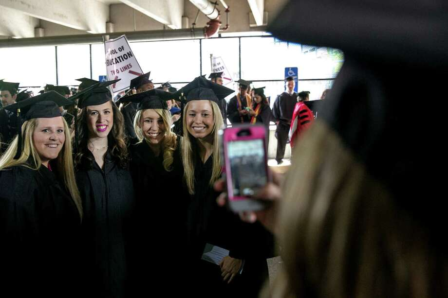 Mike Ross Connecticut Post freelance -Southern Connecticut State University students (from left to right) Emily O'Connor, Nicole Akman, Kelly Zimmerman and Melissa Peterson have their group photo taken by friend Alexandra Tarca at stagging area on Friday morning graduation at Webster Bank Arena in Bridgeport. Photo: Mike Ross / Connecticut Post contributed