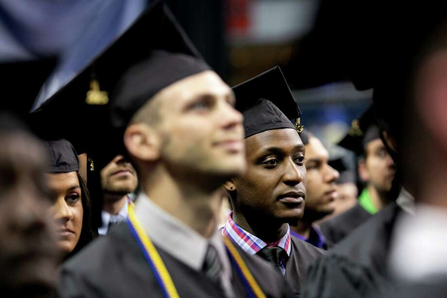 Mike Ross Connecticut Post freelance -Southern Connecticut State University student Daniel Ndamwizeye who goes by Daniel Trust stands at attenion for the pledge of allegiance during Friday morning commencement exercise at Webster Bank Arena. Trust is a Rwandan refugee. He is from Bridgeport and graduated from Bassick High and is working at TD Bank in Fairfield. He was orphaned as a young boy during the Rwandan genocide of 1994. His mother was beaten to death when he was 5 years old, and his father and sisters were also killed. Somehow Daniel survived. He went with his sisterâÄôs finance to Zambia when he was 11. Four years later, he got a visa to come to the U.S. He will be getting a bachelorâÄôs degree in business administration. Photo: Mike Ross / Connecticut Post contributed