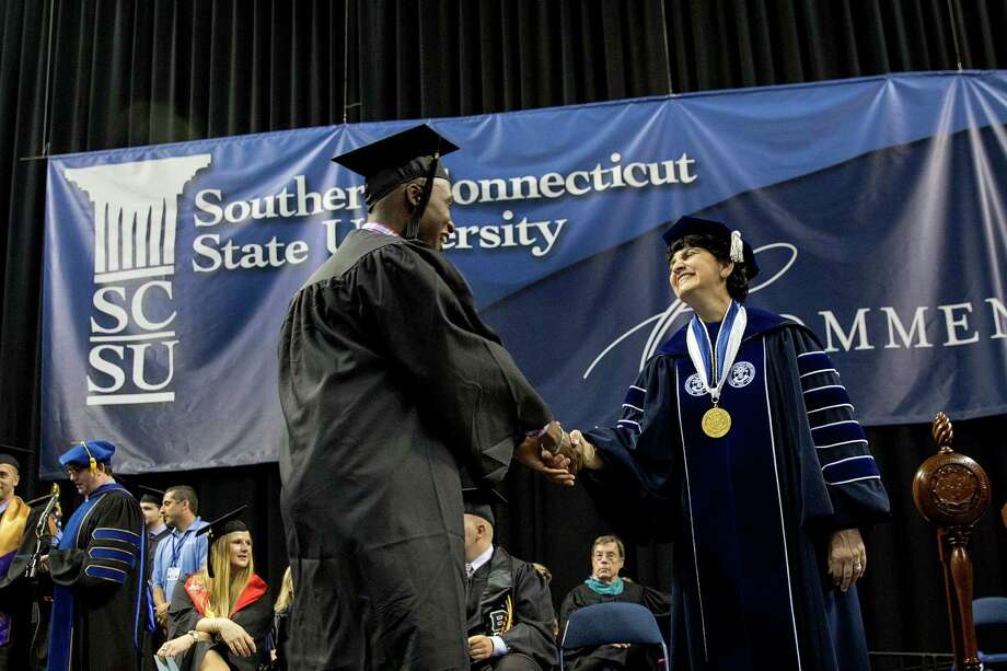 Mike Ross Connecticut Post freelance -Southern Connecticut State University student Daniel Ndamwizeye who goes by Daniel Trust shakes the hand of SCSU President Mary A. Papazian while receiving his diploma for BA in Business Adminstration during Friday morning commencement exercise at Webster Bank Arena. Trust is a Rwandan refugee. He is from Bridgeport and graduated from Bassick High and is working at TD Bank in Fairfield. He was orphaned as a young boy during the Rwandan genocide of 1994. His mother was beaten to death when he was 5 years old, and his father and sisters were also killed. Somehow Daniel survived. He went with his sisterâÄôs finance to Zambia when he was 11. Four years later, he got a visa to come to the U.S. He will be getting a bachelorâÄôs degree in business administration. Photo: Mike Ross / Connecticut Post contributed