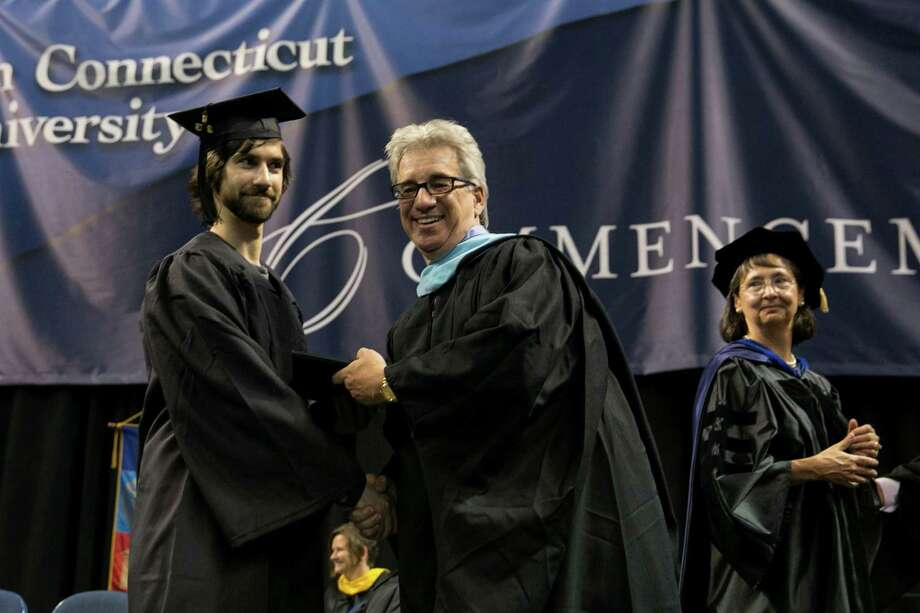 Mike Ross Connecticut Post freelance -Southern Connecticut State University student Dan Carrano receives his diploma from father Andrew Carrano, who is an adjunct faculty member in the Psychology Department during Friday morning commencement excerises at Webster Bank Arena. Dan degree will be the seventh time his family have received a diploma from SCSU. Photo: Mike Ross / Connecticut Post contributed