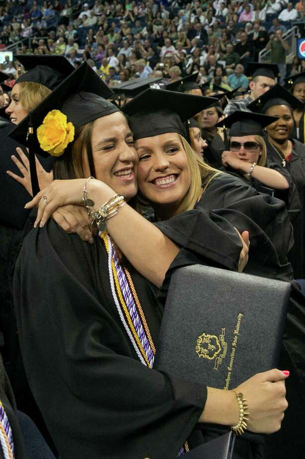 Mike Ross Connecticut Post freelance -Southern Connecticut State University students Alyssa Guard of Oxford and Lindell Carlberg of Milford hug in celebration at the end of the Friday morning commencement excerises at Webster Bank Arena. Photo: Mike Ross / Connecticut Post contributed