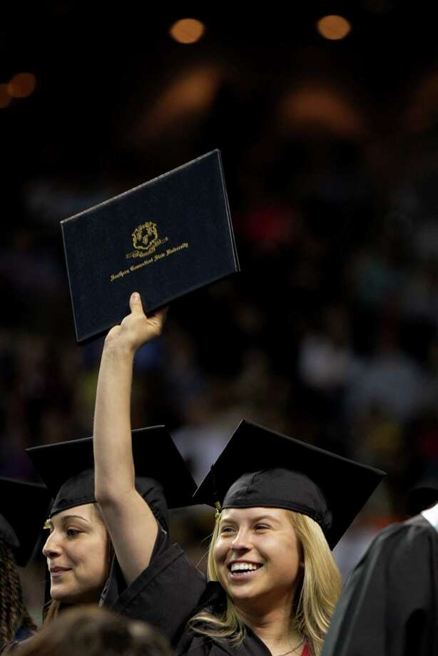 Mike Ross Connecticut Post freelance -Southern Connecticut State University student Anna Gasinski of Hamden shows her diploma to family and friends during Friday morning commencement excerises at Webster Bank Arena. Photo: Mike Ross / Connecticut Post contributed
