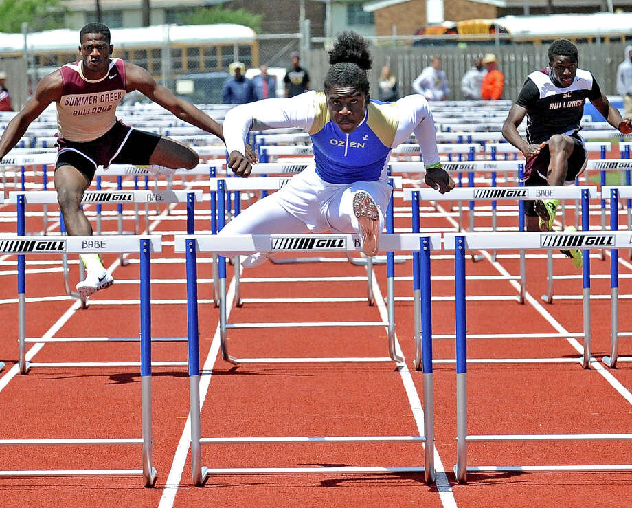 Ozen athlete Tony Brown, center, competes in the boys 110 meter hurdles during the 4A area track meet at Babe Zaharias Stadium on Friday, April 19, 2013. Photo taken: Randy Edwards/The Enterprise Photo: Randy Edwards
