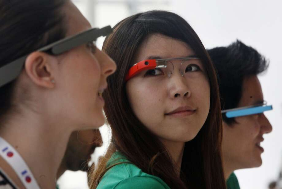 Audrey Lin (center), Google software engineer, wears a pair of Google Glass, while working at the Google Glass booth during Google I/O 2013 at Moscone West on Thursday, May 16, 2013 in San Francisco, Calif.