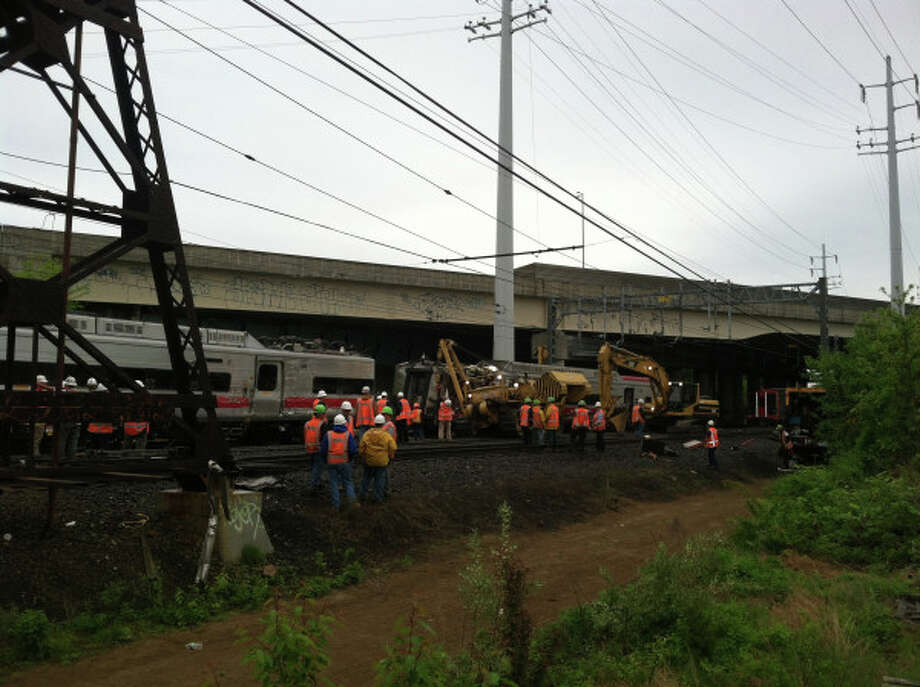 Crews on Sunday, May 19, 2013 work to remove damaged cars and debris from the scene of Friday's train collision near the Fairfield Metro station. Photo: Contributed Photo