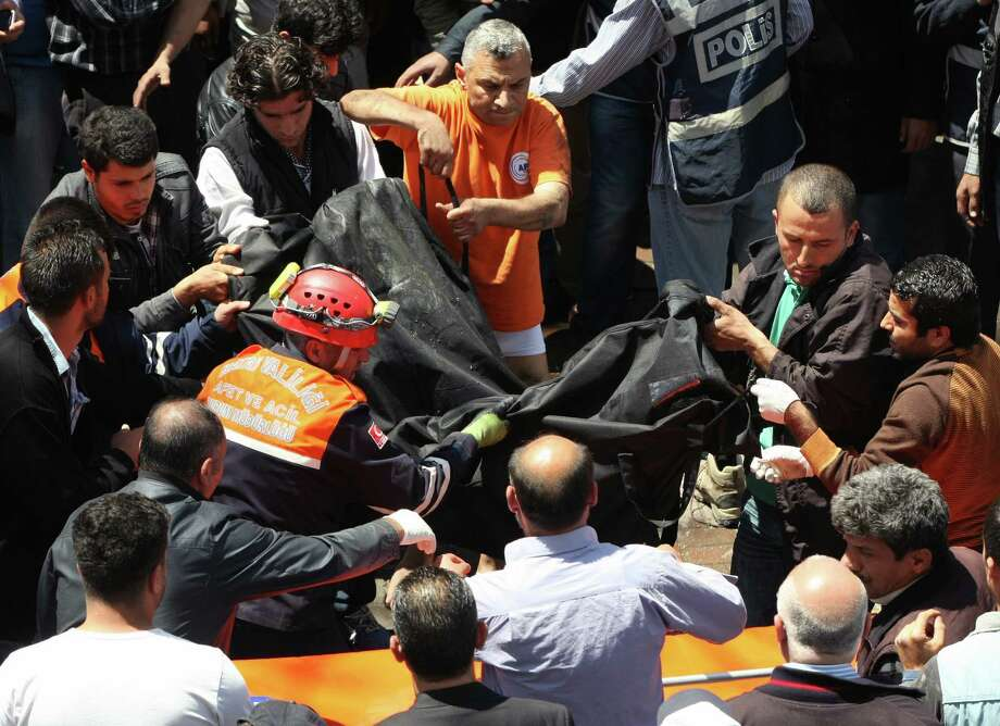 Rescue workers retreive the body of a victim found in sewerage system at the scene at one of the Saturday explosion sites that killed tens of people, in Reyhanli, near Turkey's border with Syria, Monday, May 13, 2013. The bombings on Saturday marked the biggest incident of cross-border violence since the start of Syria's bloody civil war and has the raised fear of Turkey being pulled deeper into the conflict. Photo: AP