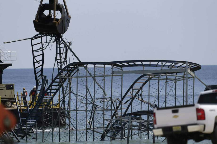 The claw of a crane, left, tears through the structure of the Jet Star Roller Coaster, Tuesday, May 14, 2013, in Seaside Heights, N.J. Workers began to demolish the roller coaster, which fell in the ocean when part of the Casino Pier was washed away by Superstorm Sandy in October. Photo: AP