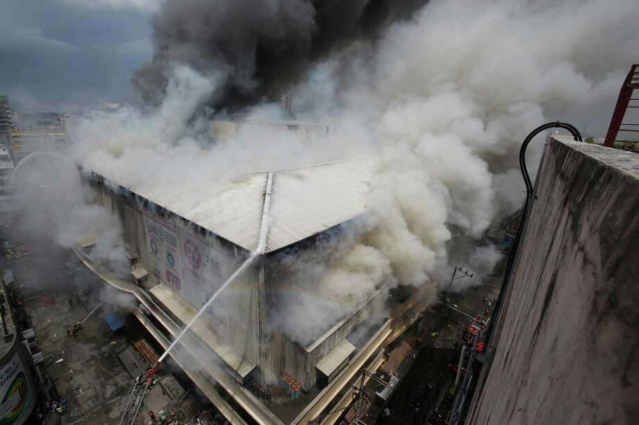 Firemen try to contain the fire at a mall in the shopping district of Divisoria in Manila, Philippines on Thursday May 16, 2013. Authorities are still determining the cause of the fire. Photo: AP