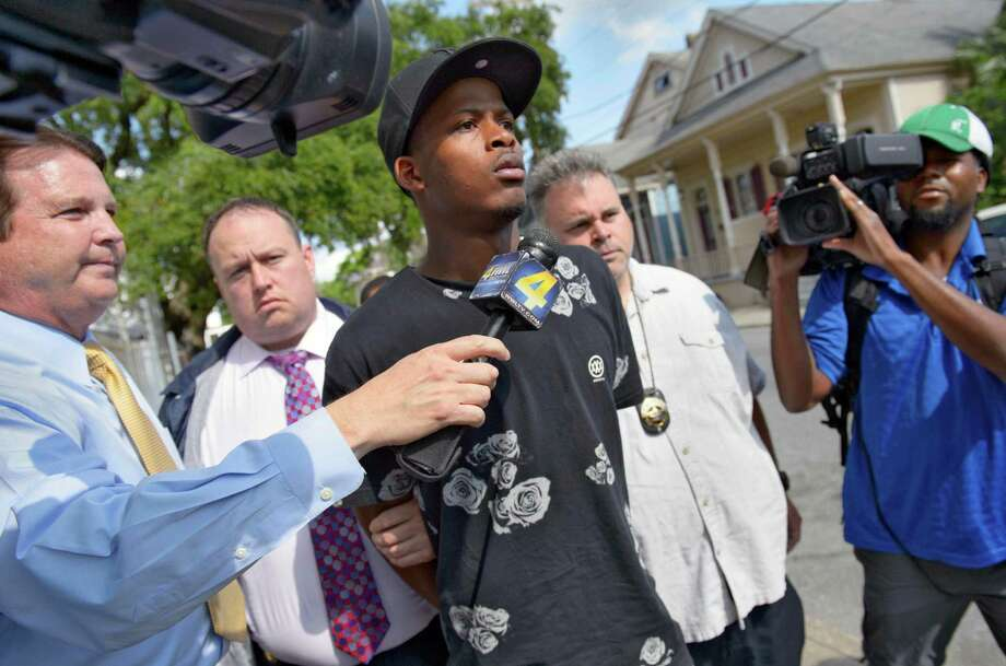 Shawn Scott, 24, a suspect in the Mother's Day parade shooting  is led out of the New Orleans 5th District Police Station, Thursday, May 16, 2013 in New Orleans. Shawn and Akein Scott. two brothers with a history of drug arrests and suspected ties to a neighborhood gang each face 20 counts of attempted second-degree murder in a shooting spree that brought a sudden bloody end to a neighborhood Mother's Day parade. Photo: AP