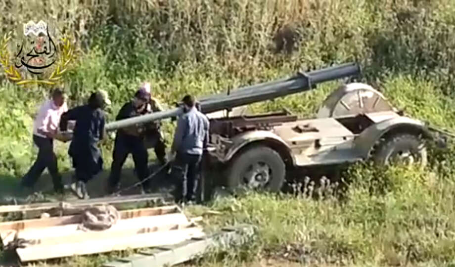 This image taken from video obtained from Ugarit News, which has been authenticated based on its contents and other AP reporting, shows Syrian rebels preparing to fire a rocket at Mannagh air base in Aleppo province, Syria, Monday, May 13, 2013. The Syrian government wants more details before deciding whether to take part in a proposed U.S.-Russian initiative to negotiate a peaceful end to Syria's crisis, the country's information minister said, staking out a similar position to the main opposition group. Photo: AP