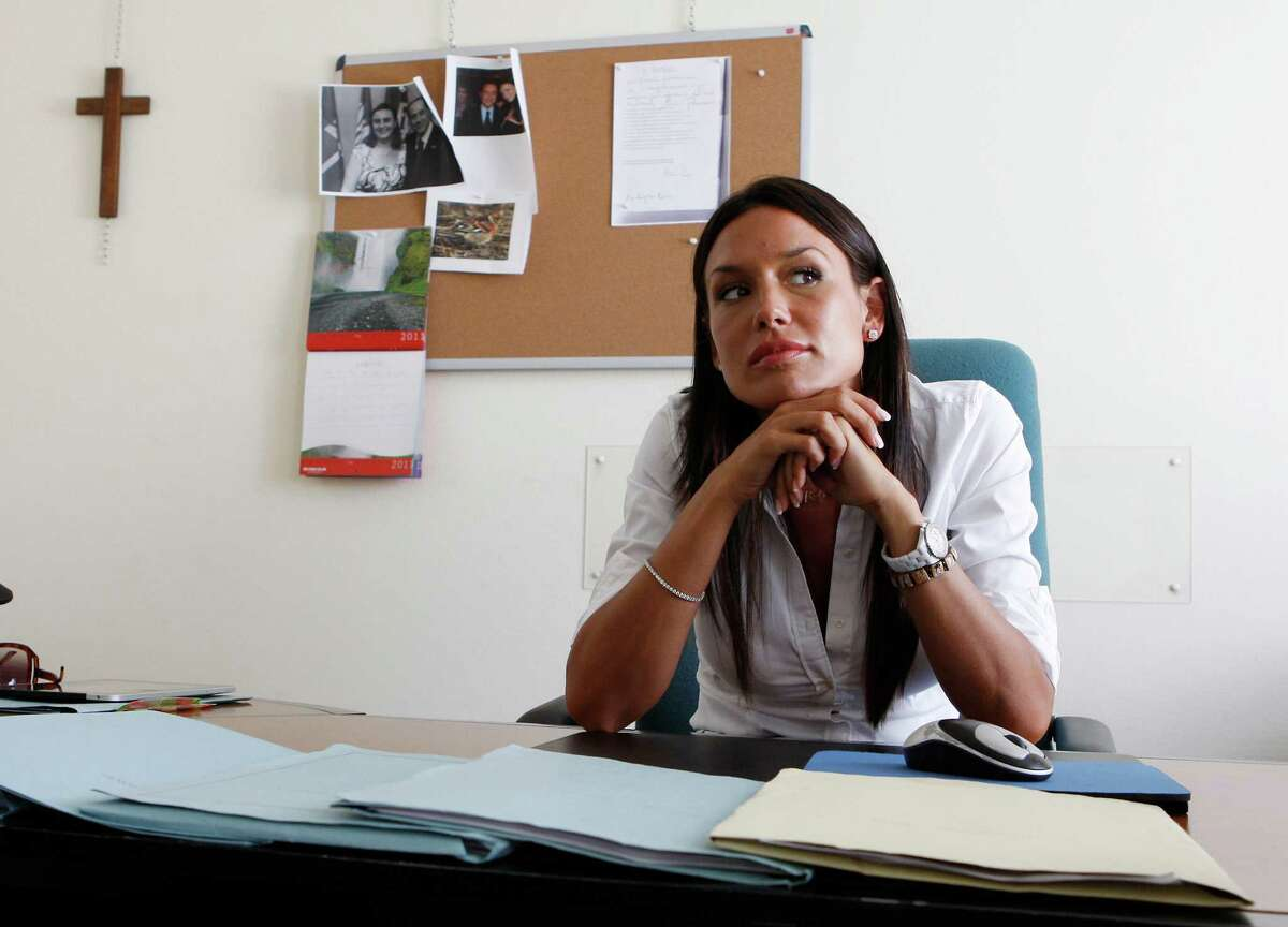 In this July 28, 2011 file photo, then Lombardy region councillor Nicole Minetti sits in her office, in Milan, Italy. Karima el-Mahroug, a Moroccan woman at the center of a sex scandal involving former Italian Premier Silvio Berlusconi, testified in Milan's courthouse, Italy, for the first time Friday, May 17, 2013 in the trial of three Berlusconi aides charged with recruiting her and other women for prostitution. El-Mahroug said one of the defendants, Nicole Minetti, had dressed up like a nun at a party at Berlusconi's villa outside Milan, and lifted her costume to show off her legs as she danced in the disco, which was outfitted with a lap-dance pole. El-Mahroug demonstrated from her seat how Minetti had raised her hemline. She said Minetti eventually took off her costume and was in just her lingerie. The trial is separate from one in which Berlusconi himself is charged with paying for sex with a minor and trying to cover it up. The three aides - Emilio Fede, an executive in Berlusconi's media empire; Minetti, a former dental hygienist, showgirl and local politician, and talent agent Dario