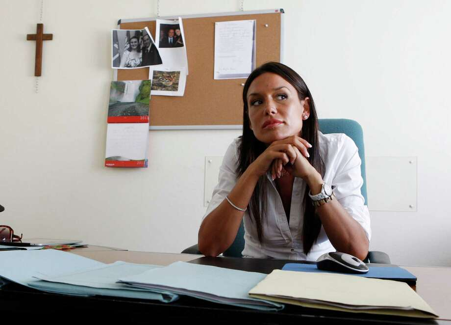 "In this July 28, 2011 file photo, then Lombardy region councillor Nicole Minetti sits in her office, in Milan, Italy. Karima el-Mahroug, a Moroccan woman at the center of a sex scandal involving former Italian Premier Silvio Berlusconi, testified in Milan's courthouse, Italy, for the first time Friday, May 17, 2013 in the trial of three Berlusconi aides charged with recruiting her and other women for prostitution. El-Mahroug said one of the defendants, Nicole Minetti, had dressed up like a nun at a party at Berlusconi's villa outside Milan, and lifted her costume to show off her legs as she danced in the disco, which was outfitted with a lap-dance pole. El-Mahroug demonstrated from her seat how Minetti had raised her hemline. She said Minetti eventually took off her costume and was in just her lingerie. The trial is separate from one in which Berlusconi himself is charged with paying for sex with a minor and trying to cover it up. The three aides - Emilio Fede, an executive in Berlusconi's media empire; Minetti, a former dental hygienist, showgirl and local politician, and talent agent Dario ""Lele"" Mora - are accused of recruiting women for prostitution at the parties and abetting prostitution, including of a minor. They deny the charges. Photo: AP"