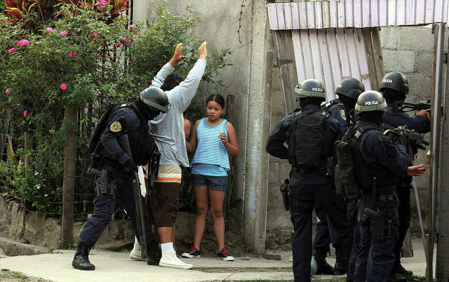 In this April 7, 2013 photo, police frisk a man as they break into a home during a shootout that ended in two suspects killed and one officer injured as police carry out an offensive against gang members in Tegucigalpa, Honduras. The officers had surrounded a house where two gangsters had holed up after a chase with police. Photo: AP