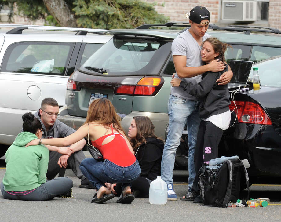 Hofstra University students gather near the house where another student and an armed intruder were killed during an overnight house break-in next to the campus, Friday, May 17, 2013, in Uniondale, N.Y. Photo: AP