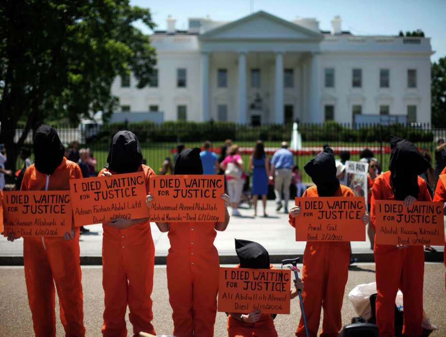Human rights activists, wearing orange prison garb and black hoods to represent the prisoners at Guantanamo Bay, Cuba, stand on Pennsylvania Avenue in front of the White House in Washington, Friday, May 17, 2013, to protest that it has not been closed down by President Obama. Photo: AP