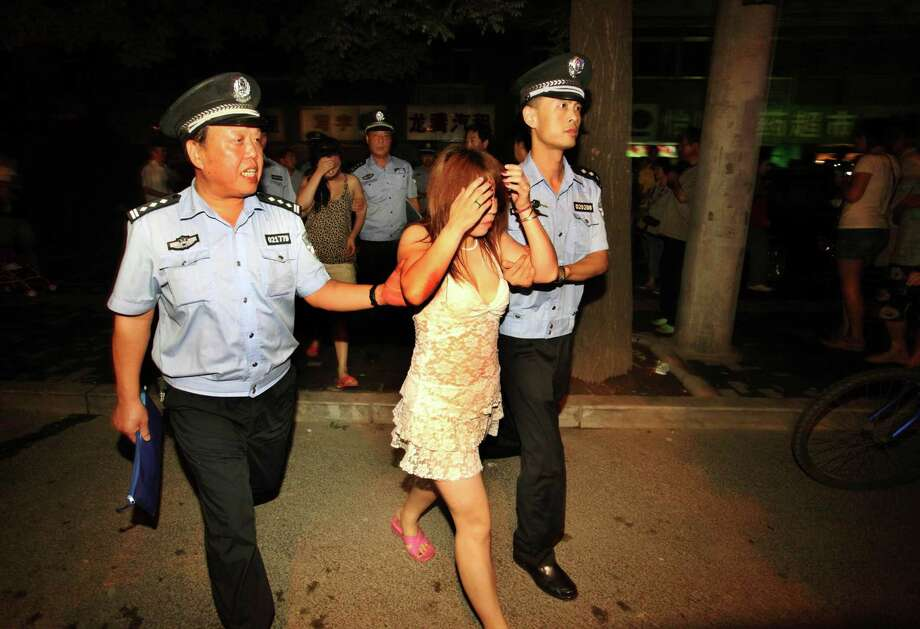 In this Aug. 13, 2010 photo, policemen detain suspected prostitutes in a campaign to crack down on prostitution in Xi'an, in northwestern China's Shaanxi province. Police in China frequently beat, torture and arbitrarily detain suspected sex workers, often with little or no evidence that they engaged in prostitution, Human Rights Watch said in a report Tuesday, May 14, 2013, calling on the government to discipline abusive officers. (AP Photo)  Photo: AP