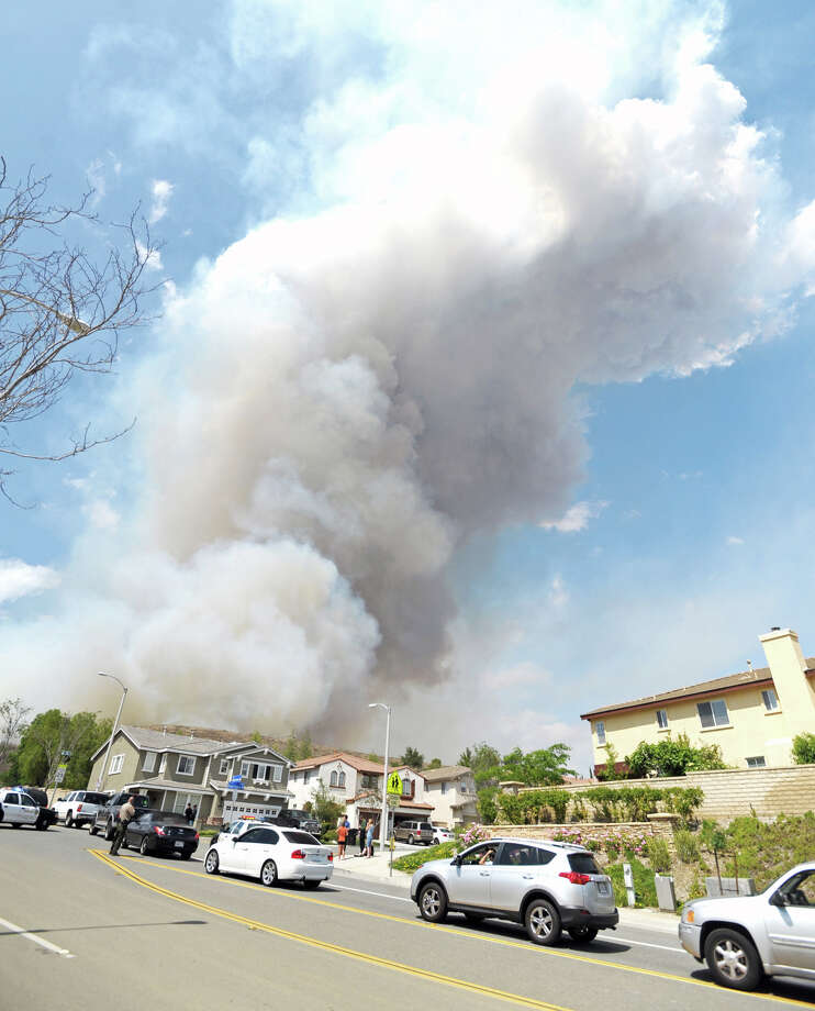 Smoke billows over a neighborhood in Castaic, Calif., as parents line up in their cars along to pick up students from a nearby elementary school, Friday, May 17, 2013. As firefighters took on a stubborn 3-day-old wildfire Friday in rough terrain north of Los Angeles, a second and more serious blaze broke out 30 miles away near Interstate 5, quickly surging to more than 500 acres, briefly threatening an elementary school and leading to the precautionary evacuation of nearly 20 homes.  (AP Photo/Santa Clarita Valley Signal, Jonathan Pobre)  Photo: AP