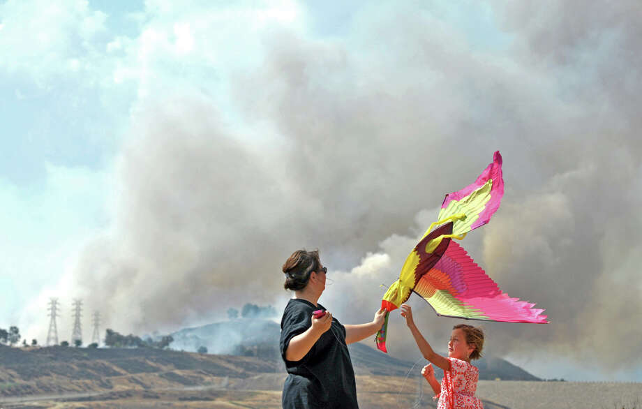 Jodi Carter, left, and her daughter Camryn, 7, play with a kite as they watch smoke from a brush fire from Lake Hughes Road in Castaic, Calif., Friday, May 17, 2013. (AP Photo/Santa Clarita Valley Signal, Jonathan Pobre)  Photo: AP