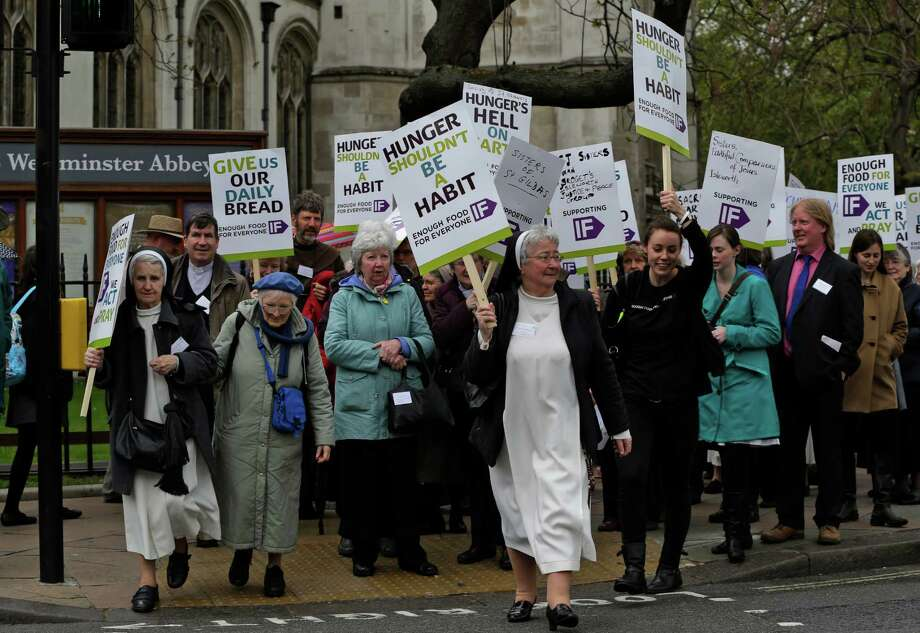 Nuns, priests and supporters hold placards as they march during a protest in central London, Wednesday, May 15, 2013. Hundreds of members of religious orders, priests and supporters marched to Britain's Houses of Parliament to push for action on global hunger. The mass lobby has been organized by UK based Catholic development agency CAFOD as part of the 'Enough Food for Everyone IF' campaign. The IF initiative is a coalition of more than 170 organizations which have joined together to campaign for action by G8 countries on the issue of worldwide hunger. Photo: AP