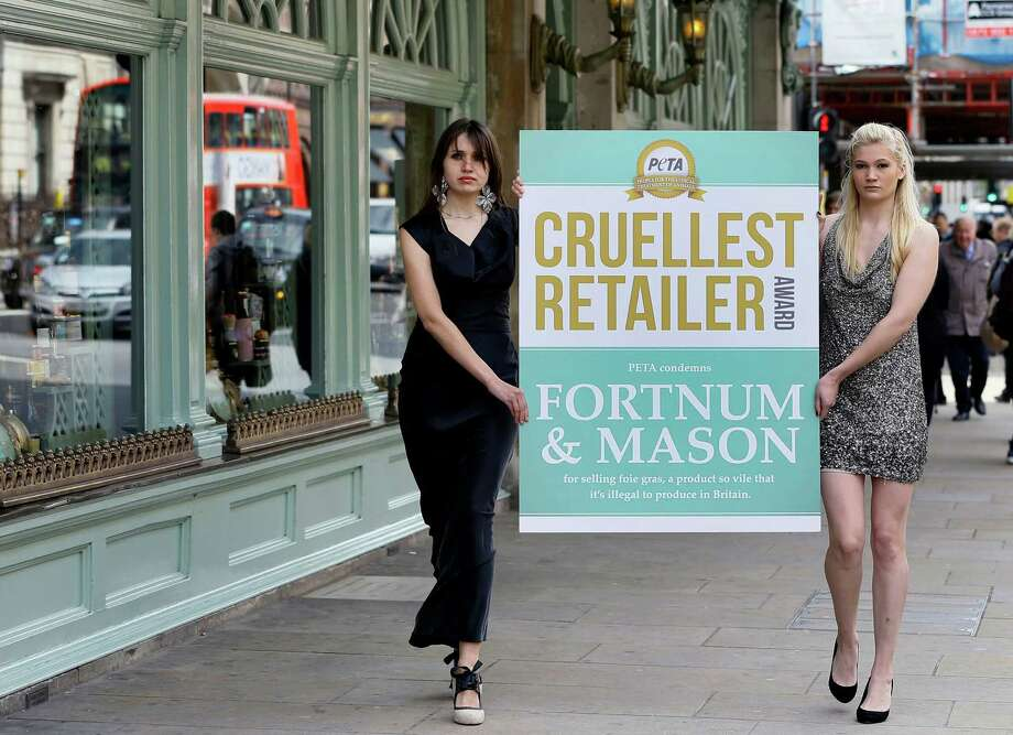 Margarita Ustimenko, centre, and Hope Carveth carry the Cruellest Retailer Award outside the Fortnum and Mason department store, in London, Monday, May 13, 2013. Fortnum and Mason were awarded the Cruellest Retailer Award by animal welfare group PETA, for being one of the few remaining retailers to sell Foie Gras, the production of which is outlawed in the United Kingdom due to the barbaric and hideous way it is produced. Photo: AP