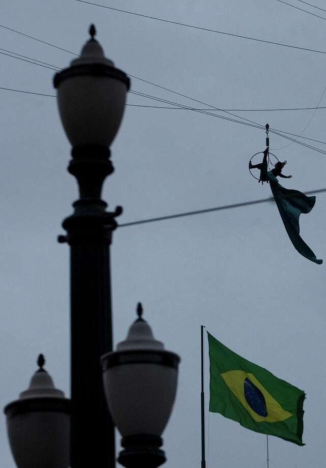 An artist hangs from a wire cable during a performance as part of the annual art event, Virada Cultural in Sao Paulo, Brazil, Saturday, May 18, 2013. The Virada Cultural or Cultural Turn, is an annual event organized, since 2005, to promote the city of Sao Paulo with 24 hours of uninterrupted artistic attractions that include music concerts, dance, cooking and theater. Photo: AP
