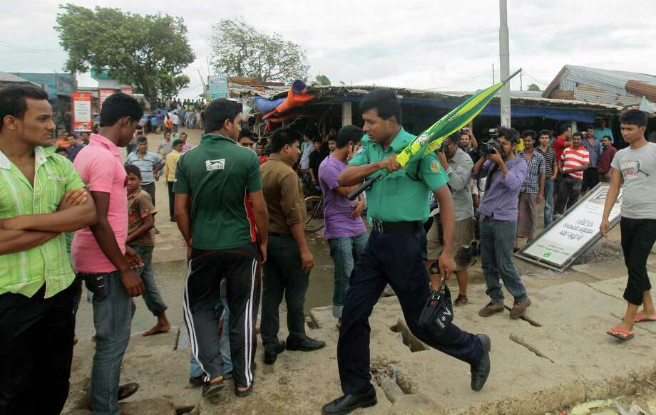 A Bangladeshi police officer uses force to evacuate people standing by the Bay of Bengal coast, before Cyclone Mahasen made landfall in Chittagong, Bangladesh, Thursday, May 16, 2013. Cyclone Mahasan weakened Thursday afternoon into a tropical storm with at least 18 deaths reported in Bangladesh, Myanmar and Sri Lanka, but officials had prepared for a far greater storm. Bangladesh evacuated 1 million people from coastal areas and the United Nations warned that 8.2 million people could face life-threatening conditions. Photo: AP