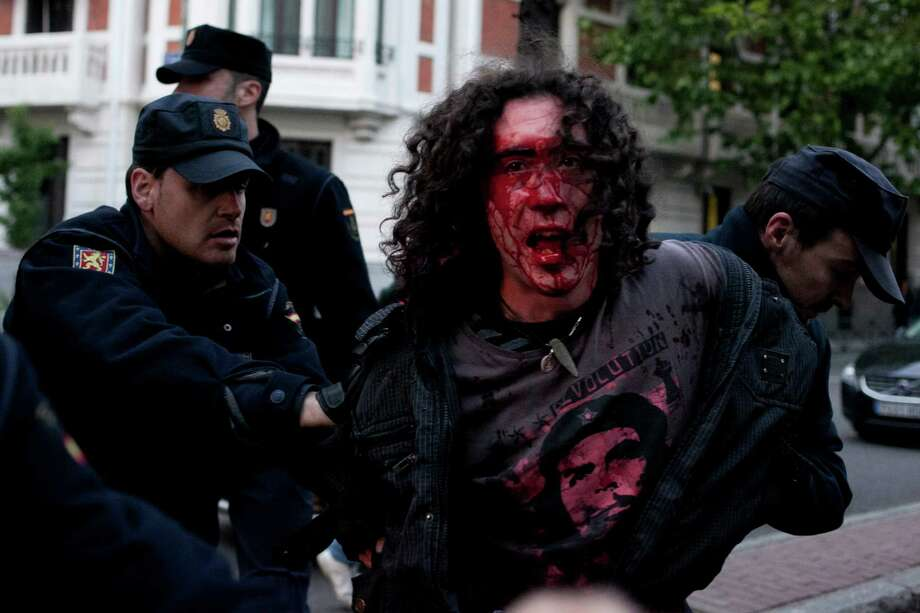 An abortion rights activist is detained by police officers during a protest to condemn the government plan for abortion reform in Madrid Spain, Thursday, May 16, 2013. Photo: AP