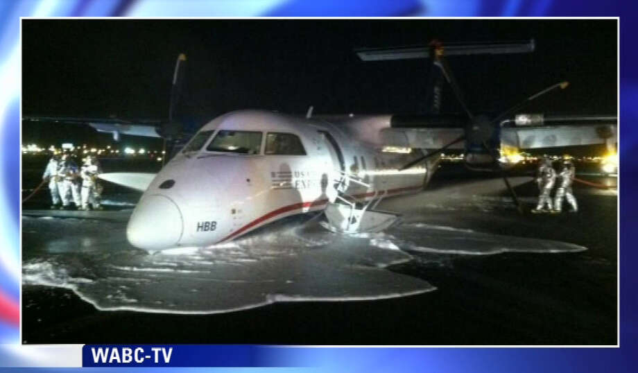In this image taken from video and provided to WABC TV News by an airport source, emergency personnel spray foam on the fuselage of a US Airways Express commuter plane after it made a belly landing at Newark Liberty International Airport, Saturday, May 18, 2013, in Newark, N.J. The turboprop plane reportedly left Philadelphia shortly before 11 p.m., Friday, and landed safely at Newark with its landing gear retracted at about 1 a.m., Saturday. There were no injuries. (AP Photo/WABC TV News)  Photo: AP