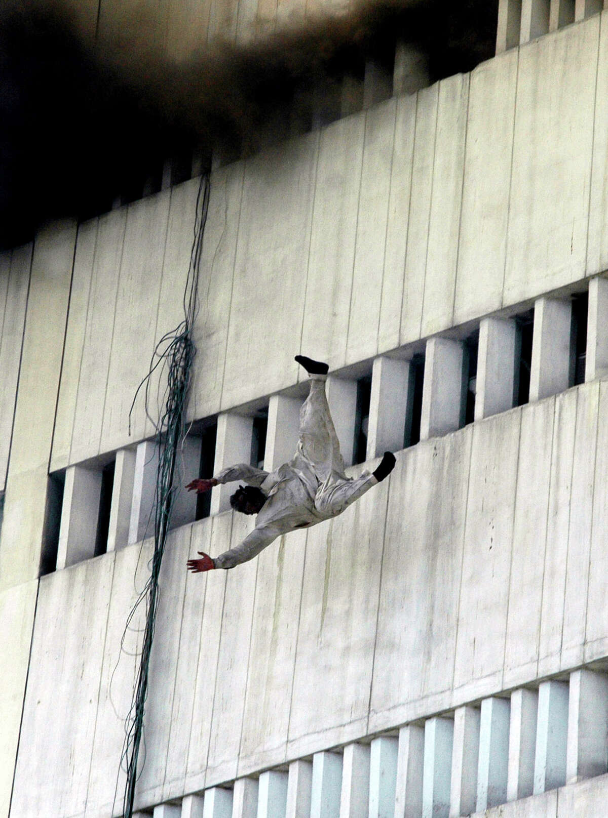 A man jumps from the fifth floor of a burning government building in Lahore, Pakistan on Thursday, May 9, 2013. The fire spread to to three floors of the 13-story building.