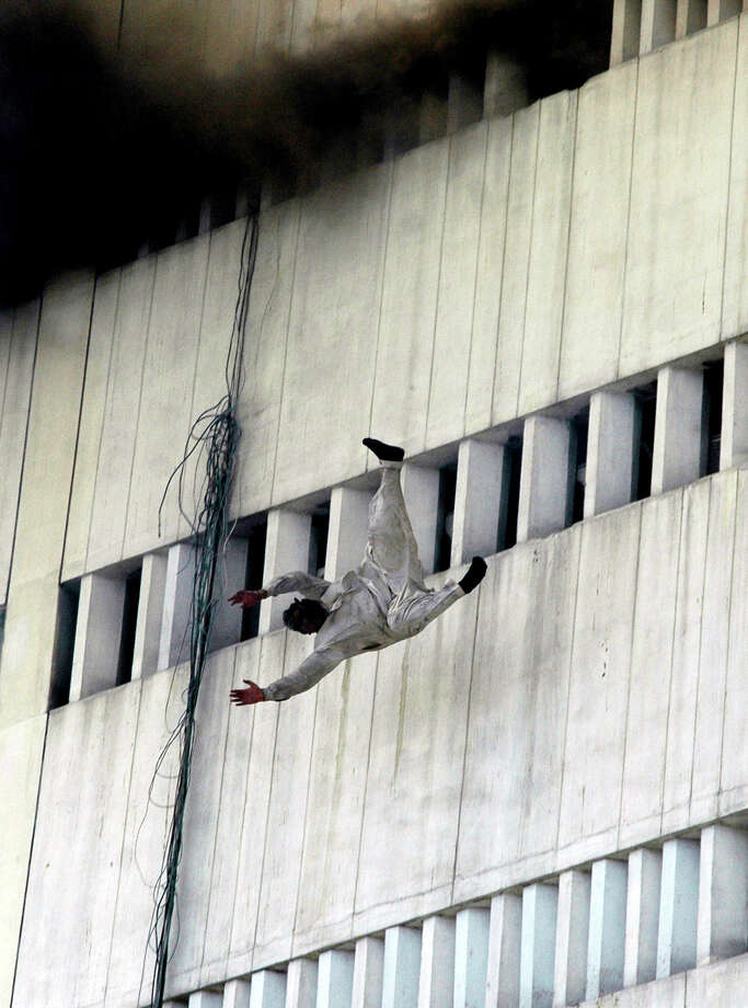 A man jumps from the fifth floor of a burning government building in Lahore, Pakistan on Thursday, May 9, 2013. The fire spread to to three floors of the 13-story building. Photo: AP