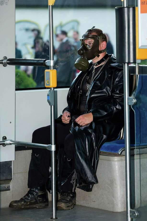 A man wearing black clothing and a gas mask sits in the tramway car on the second day of the annual Wave-Gotik Treffen, or Wave and Goth Festival, on May 18, 2013 in Leipzig, Germany. The four-day festival, in which elaborate fashion is a must, brings together over 20,000 Wave, Goth and steam punk enthusiasts from all over the world for concerts, readings, films, a Middle Ages market and workshops. Photo: Marco Prosch, Getty Images / 2013 Marco Prosch