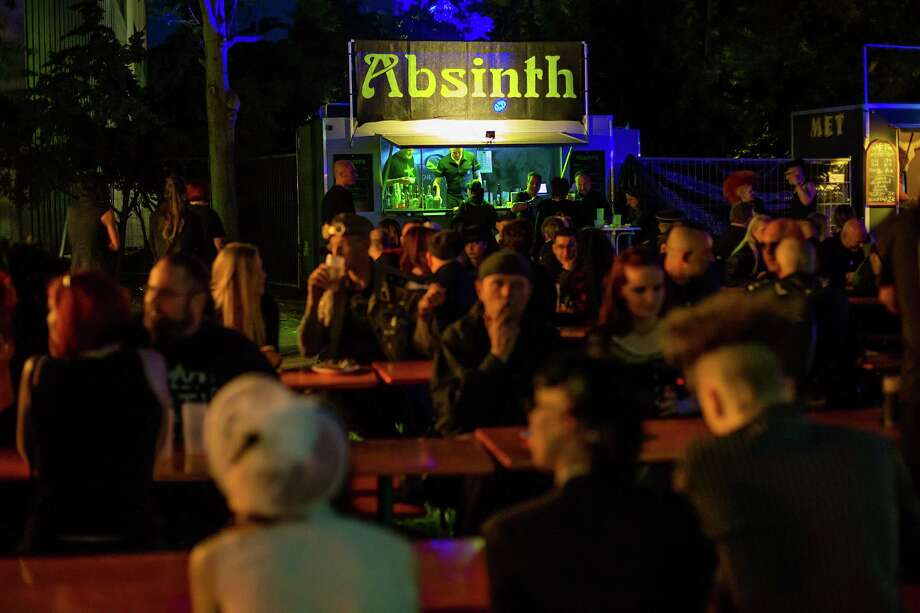 Participants sit in front of a booth selling absinth on the first day of the annual Wave-Gotik Treffen, or Wave and Goth Festival, on May 17, 2013 in Leipzig, Germany. The four-day festival, in which elaborate fashion is a must, brings together over 20,000 Wave, Goth and steam punk enthusiasts from all over the world for concerts, readings, films, a Middle Ages market and workshops. Photo: Marco Prosch, Getty Images / 2013 Getty Images