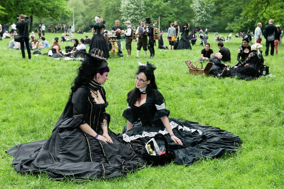 Two women in black Victorian clothing sit on the lawn and chat during the traditional park picnic on the first day of the annual Wave-Gotik Treffen, or Wave and Goth Festival, on May 17, 2013 in Leipzig, Germany. The four-day festival, in which elaborate fashion is a must, brings together over 20,000 Wave, Goth and steam punk enthusiasts from all over the world for concerts, readings, films, a Middle Ages market and workshops. Photo: Marco Prosch, Getty Images / 2013 Getty Images