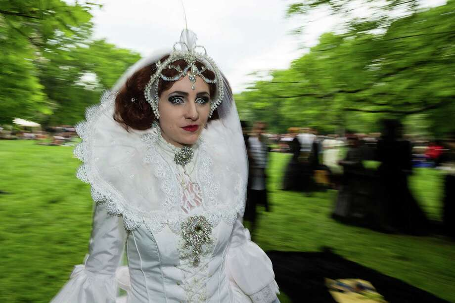 A woman in a white dress with fake wolf's eyes rushes by during the traditional park picnic on the first day of the annual Wave-Gotik Treffen, or Wave and Goth Festival, on May 17, 2013 in Leipzig, Germany. The four-day festival, in which elaborate fashion is a must, brings together over 20,000 Wave, Goth and steam punk enthusiasts from all over the world for concerts, readings, films, a Middle Ages market and workshops. Photo: Marco Prosch, Getty Images / 2013 Getty Images
