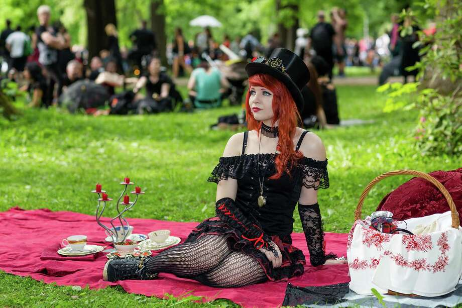 A girl sits on a red blanket on the lawn during the traditional park picnic on the first day of the annual Wave-Gotik Treffen, or Wave and Goth Festival, on May 17, 2013 in Leipzig, Germany. The four-day festival, in which elaborate fashion is a must, brings together over 20,000 Wave, Goth and steam punk enthusiasts from all over the world for concerts, readings, films, a Middle Ages market and workshops. Photo: Marco Prosch, Getty Images / 2013 Getty Images