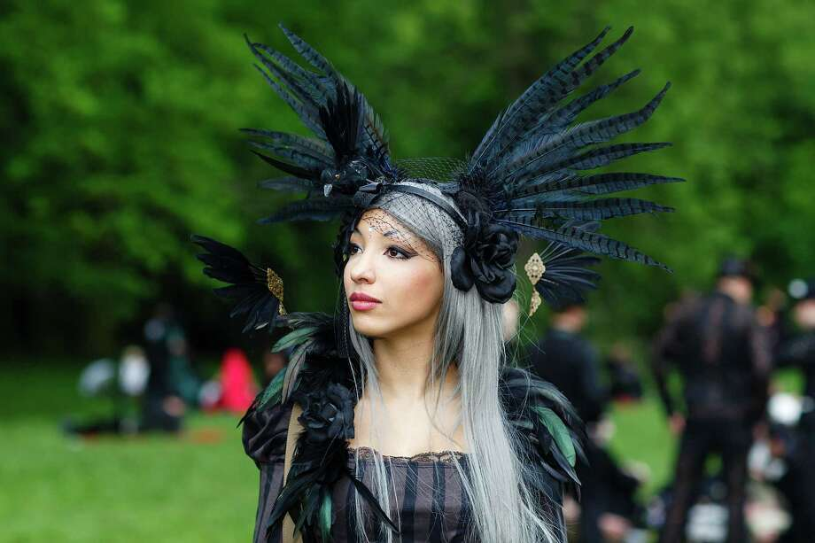 A woman in black clothing wearing a feather-hat poses for pictures during the traditional park picnic on the first day of the annual Wave-Gotik Treffen, or Wave and Goth Festival, on May 17, 2013 in Leipzig, Germany. The four-day festival, in which elaborate fashion is a must, brings together over 20,000 Wave, Goth and steam punk enthusiasts from all over the world for concerts, readings, films, a Middle Ages market and workshops. Photo: Marco Prosch, Getty Images / 2013 Getty Images