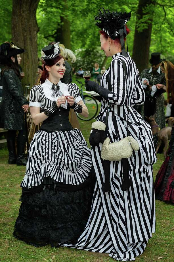 Two women in Victorian clothing and with a shawn-the-sheep-bag chat during the traditional park picnic on the first day of the annual Wave-Gotik Treffen, or Wave and Goth Festival, on May 17, 2013 in Leipzig, Germany. The four-day festival, in which elaborate fashion is a must, brings together over 20,000 Wave, Goth and steam punk enthusiasts from all over the world for concerts, readings, films, a Middle Ages market and workshops. Photo: Marco Prosch, Getty Images / 2013 Getty Images