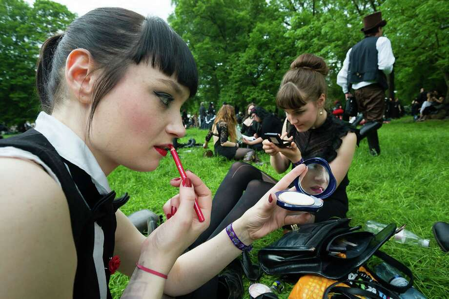 Two girls in black clothing refresh their make-up during the traditional park picnic on the first day of the annual Wave-Gotik Treffen, or Wave and Goth Festival, on May 17, 2013 in Leipzig, Germany. The four-day festival, in which elaborate fashion is a must, brings together over 20,000 Wave, Goth and steam punk enthusiasts from all over the world for concerts, readings, films, a Middle Ages market and workshops. Photo: Marco Prosch, Getty Images / 2013 Getty Images