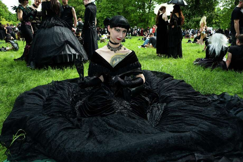 A woman in a black dress sits on the lawn during the traditional park picnic on the first day of the annual Wave-Gotik Treffen, or Wave and Goth Festival, on May 17, 2013 in Leipzig, Germany. The four-day festival, in which elaborate fashion is a must, brings together over 20,000 Wave, Goth and steam punk enthusiasts from all over the world for concerts, readings, films, a Middle Ages market and workshops. Photo: Marco Prosch, Getty Images / 2013 Getty Images