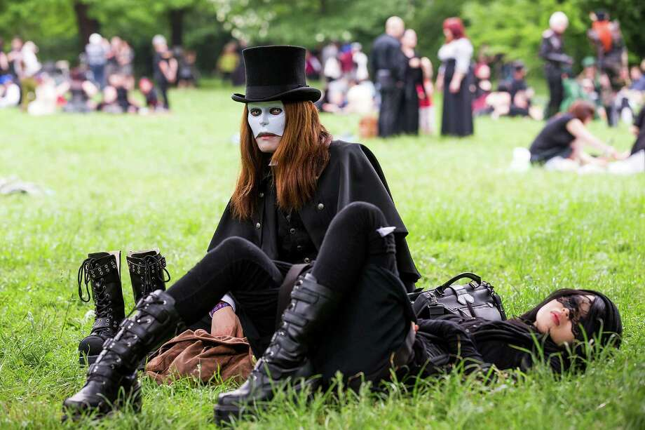 A goth couple wearing masks rest on the lawn during the traditional park picnic on the first day of the annual Wave-Gotik Treffen, or Wave and Goth Festival, on May 17, 2013 in Leipzig, Germany. The four-day festival, in which elaborate fashion is a must, brings together over 20,000 Wave, Goth and steam punk enthusiasts from all over the world for concerts, readings, films, a Middle Ages market and workshops. Photo: Marco Prosch, Getty Images / 2013 Getty Images