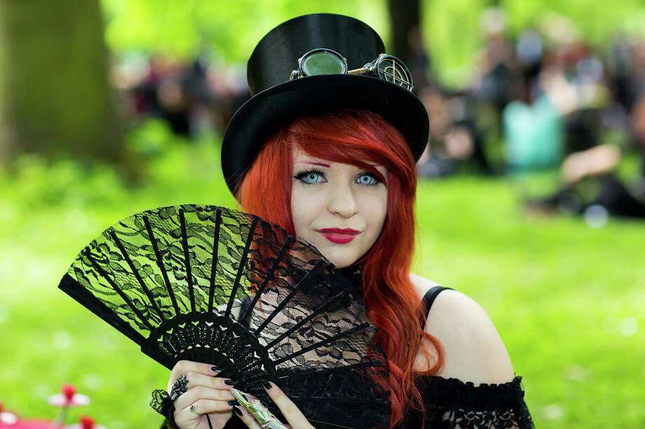 A girl with a fan attends the traditional park picnic on the first day of the annual Wave-Gotik Treffen, or Wave and Goth Festival, on May 17, 2013 in Leipzig, Germany. The four-day festival, in which elaborate fashion is a must, brings together over 20,000 Wave, Goth and steam punk enthusiasts from all over the world for concerts, readings, films, a Middle Ages market and workshops. Photo: Marco Prosch, Getty Images / 2013 Getty Images