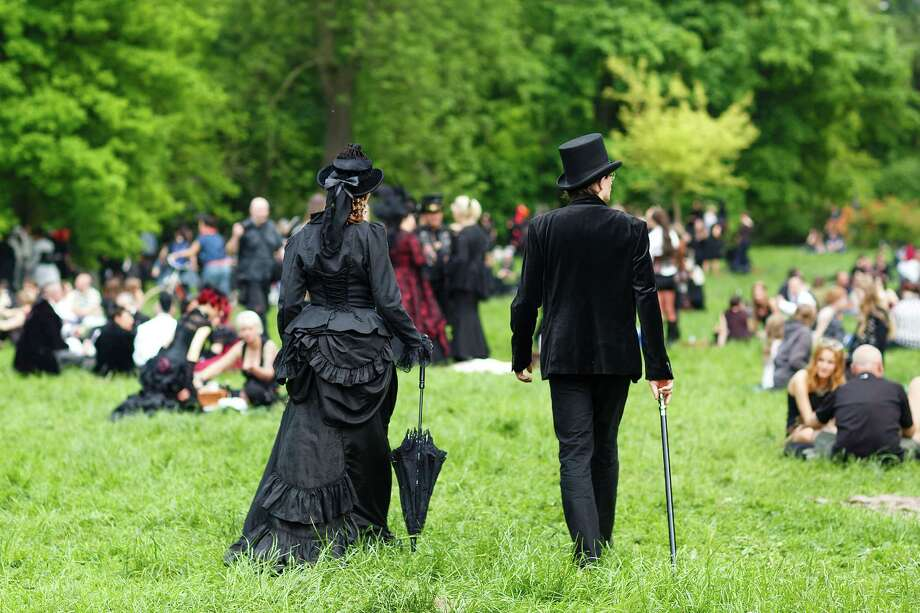 A couple in Victorian clothing walks on the lawn during the traditional park picnic on the first day of the annual Wave-Gotik Treffen, or Wave and Goth Festival, on May 17, 2013 in Leipzig, Germany. The four-day festival, in which elaborate fashion is a must, brings together over 20,000 Wave, Goth and steam punk enthusiasts from all over the world for concerts, readings, films, a Middle Ages market and workshops. Photo: Marco Prosch, Getty Images / 2013 Getty Images
